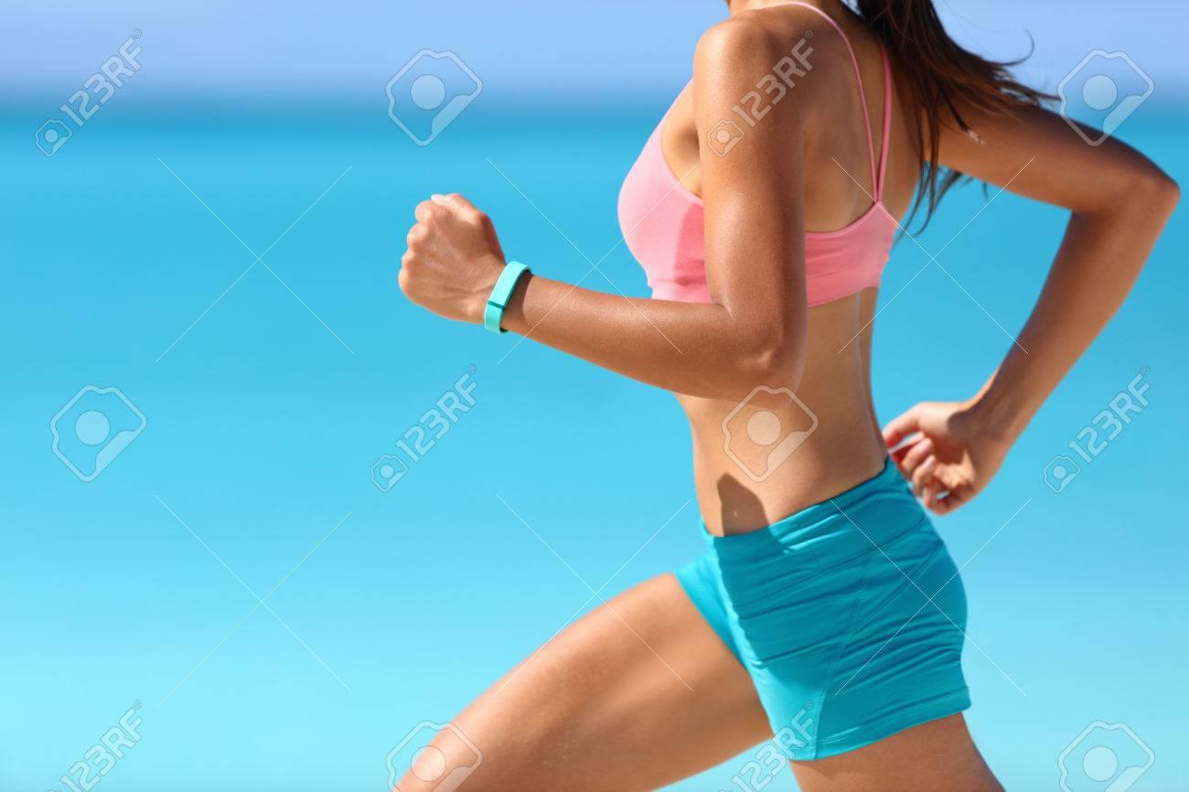 Wearable tech smart watch closeup, active woman wearing activity tracker bracelet on wrist. Runner girl running fast intense run outdoor on beach ocean background living a healthy life. Legs closeup. Stock Photo - 54454641