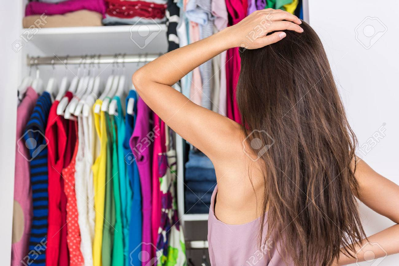Home closet indecision woman choosing her fashion outfit on clothing rack. Shopping spring cleaning concept. Morning woman having too many clothes thinking of what to wear in organized clean walk-in. Stock Photo - 55645911