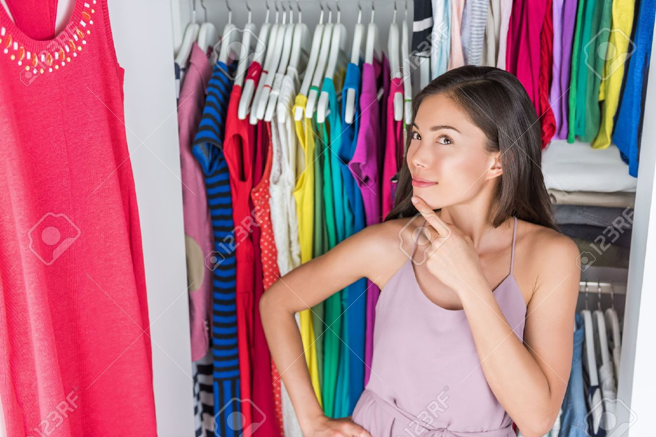 Home closet or store clothing rack changing room. Woman choosing her fashion outfit. Shopping girl thinking what to wear in front of many choices of dresses and clothes in organized clean walk-in. Banque d'images - 55645913