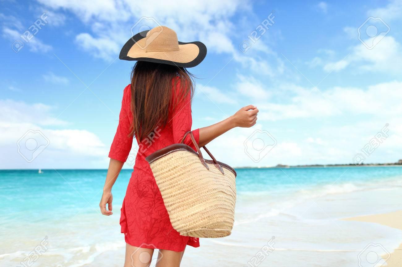 56b61bbd72 Stock Photo - Woman tourist walking on tropical summer vacation wearing sun  hat