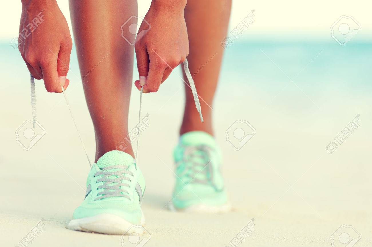 Healthy runner woman tying running shoes laces getting reay for beach jogging. Closeup of hands lacing cross training sneakers trainers for cardio workout. Female athlete living a fit and active life. Stock Photo - 55651523