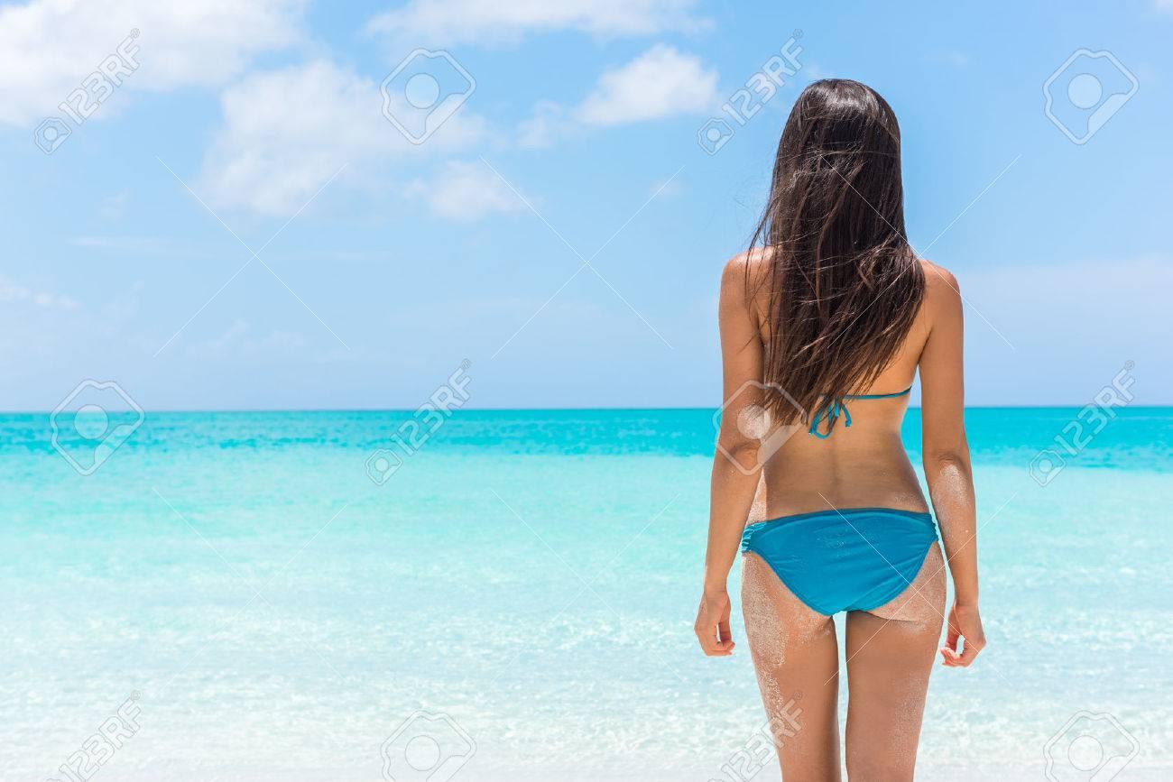 Bikini woman relaxing standing on tropical beach vacation showing off slim  sexy butt. Beautiful model