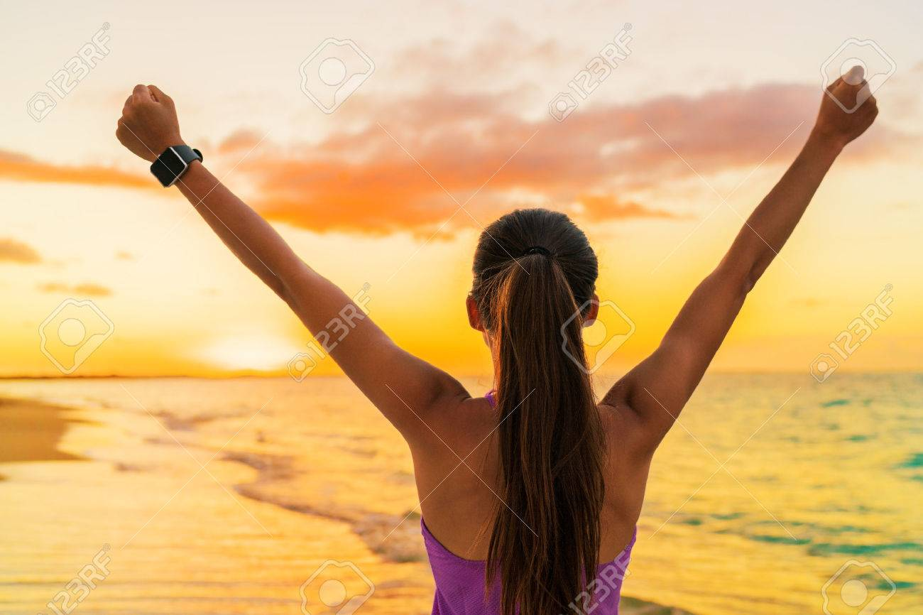 Success freedom smartwatch woman from behind at sunset. Winning goal achievement fitness athlete girl cheering on tropical summer beach wearing wearable tech smart watch activity bracelet. Banque d'images - 55651555