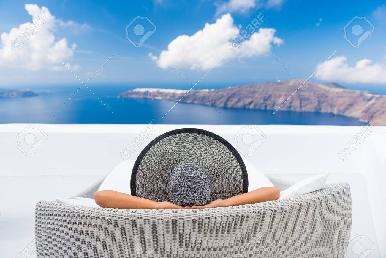 Travel vacation woman relaxing enjoying Santorini looking at famous view of Caldera. Young lady lying down on sun bed sofa lounge chair on holidays. Amazing view of sea. Europe travel destination. Stock Photo - 55652381