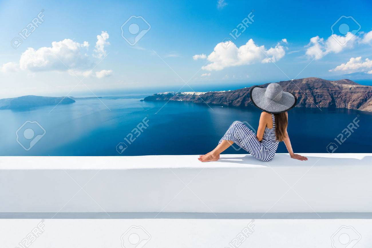 Europe Greece Santorini travel vacation. Woman looking at view on famous travel destination. Elegant young lady living fancy jetset lifestyle wearing dress on holidays. Amazing view of sea and Caldera - 55657498