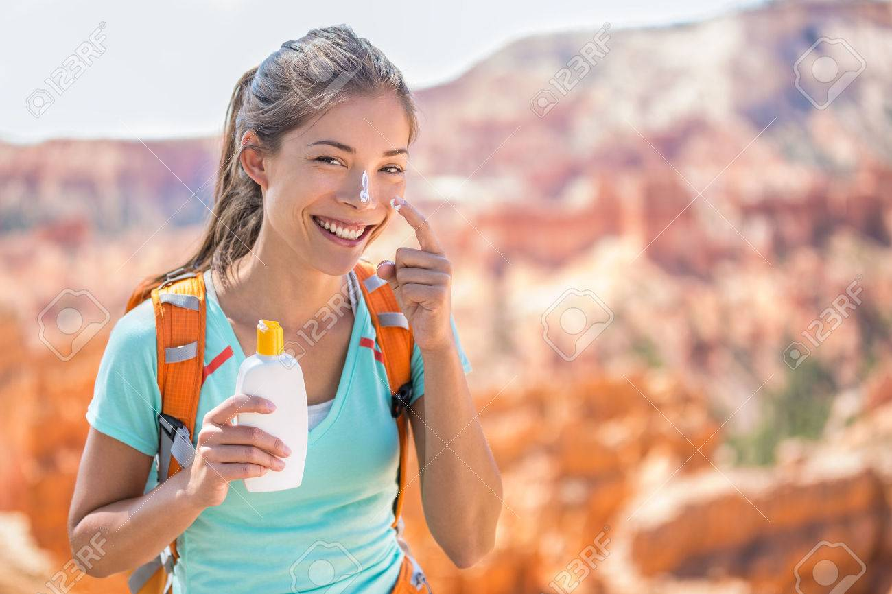 Hiker sunscreen. Woman hiking putting sunblock lotion outdoors during summer hike holidays. Mixed race Caucasian Asian female model. Stock Photo - 55657499