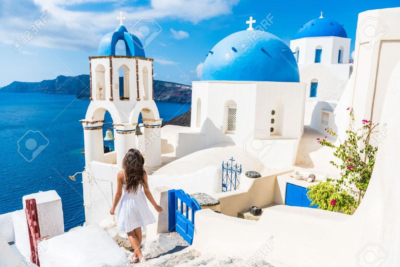 Santorini travel tourist woman on vacation in Oia walking on stairs. Person in white dress visiting the famous white village with the mediterranean sea and blue domes. Europe summer destination. Stock Photo - 55657545
