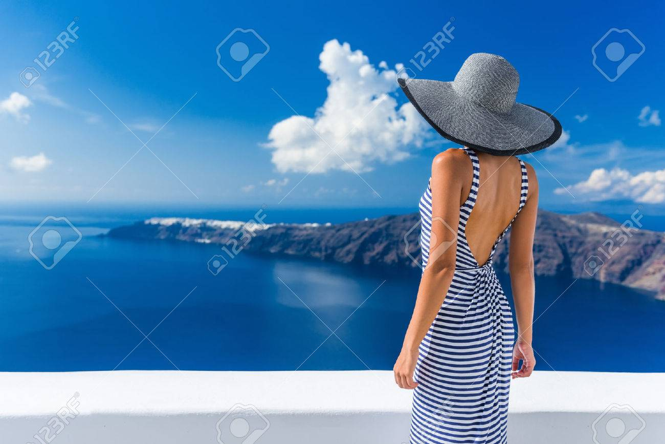 Luxury travel vacation woman looking at view on Santorini famous Europe travel destination. Elegant young lady living fancy jetset lifestyle wearing dress on holidays. Amazing view of sea and Caldera. Stock Photo - 55656558