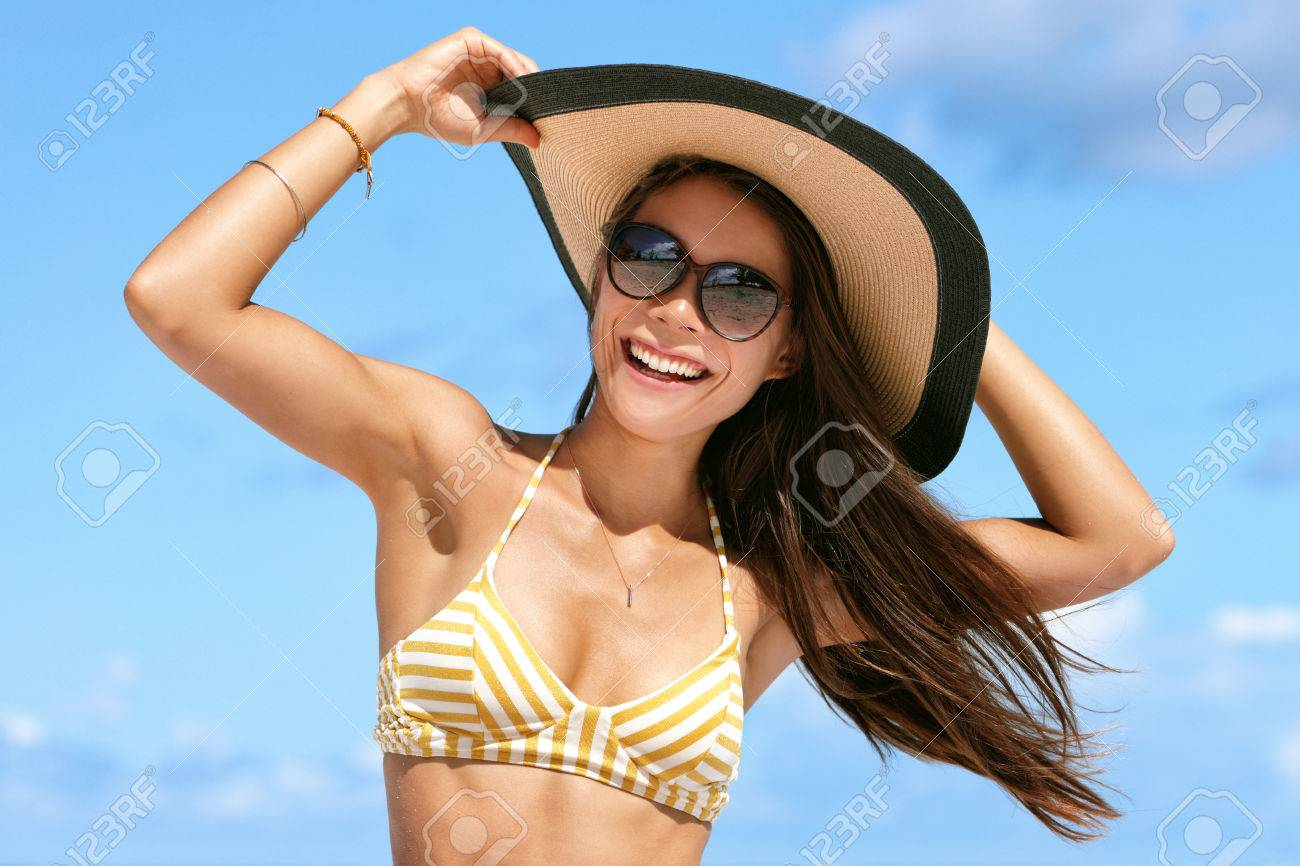 4be78a1af6d Summer beach vacation woman enjoying the sun in bikini and sunglasses  having fun happy with hair in wind holding on hat. Sexy Asian young adult  on towel for ...