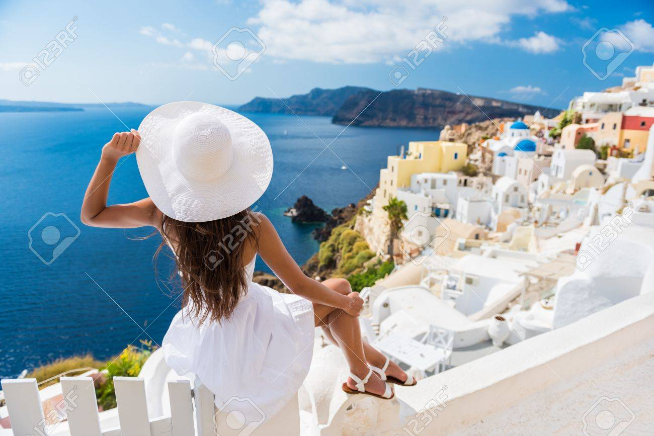Tourist woman enjoying view of beautiful white village of Oia with Caldera and mediterranean sea. Young stylish female model wearing sunhat and red dress enjoying summer travel vacation in Europe. Stock Photo - 55657659