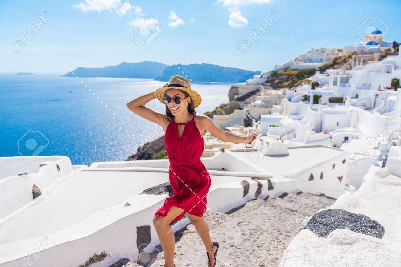 Travel Tourist Happy Woman Running Stairs Santorini, Greek Islands, Greece, Europe. Girl on summer vacation visiting famous tourist destination having fun smiling in Oia. Stock Photo - 55657674