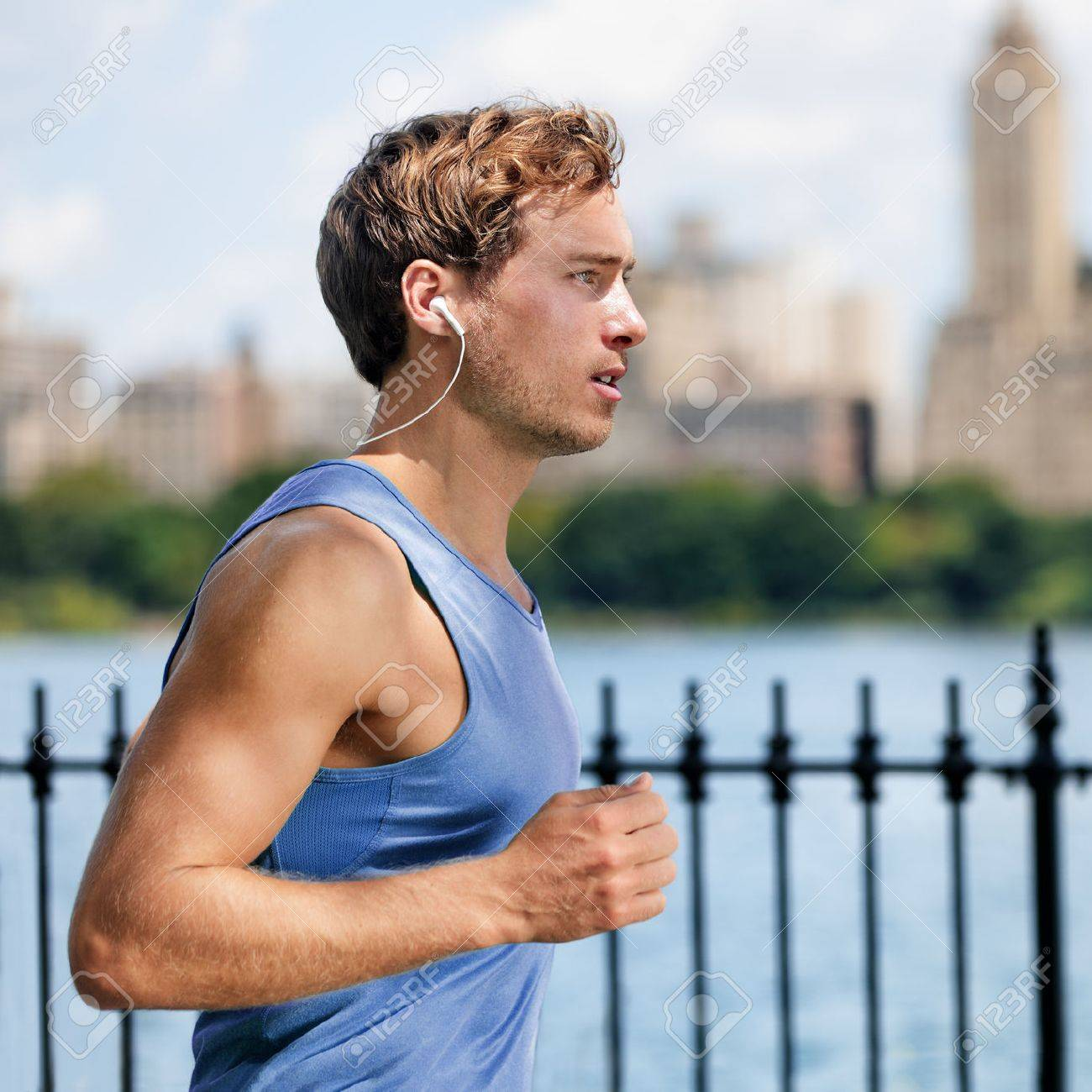 Urban young man running in city park listening to music with wireless bluetooth in-ear earphones living a healthy active lifestyle. Male runner blue top working out cardio exercise workout in summer. Stock Photo - 57342433