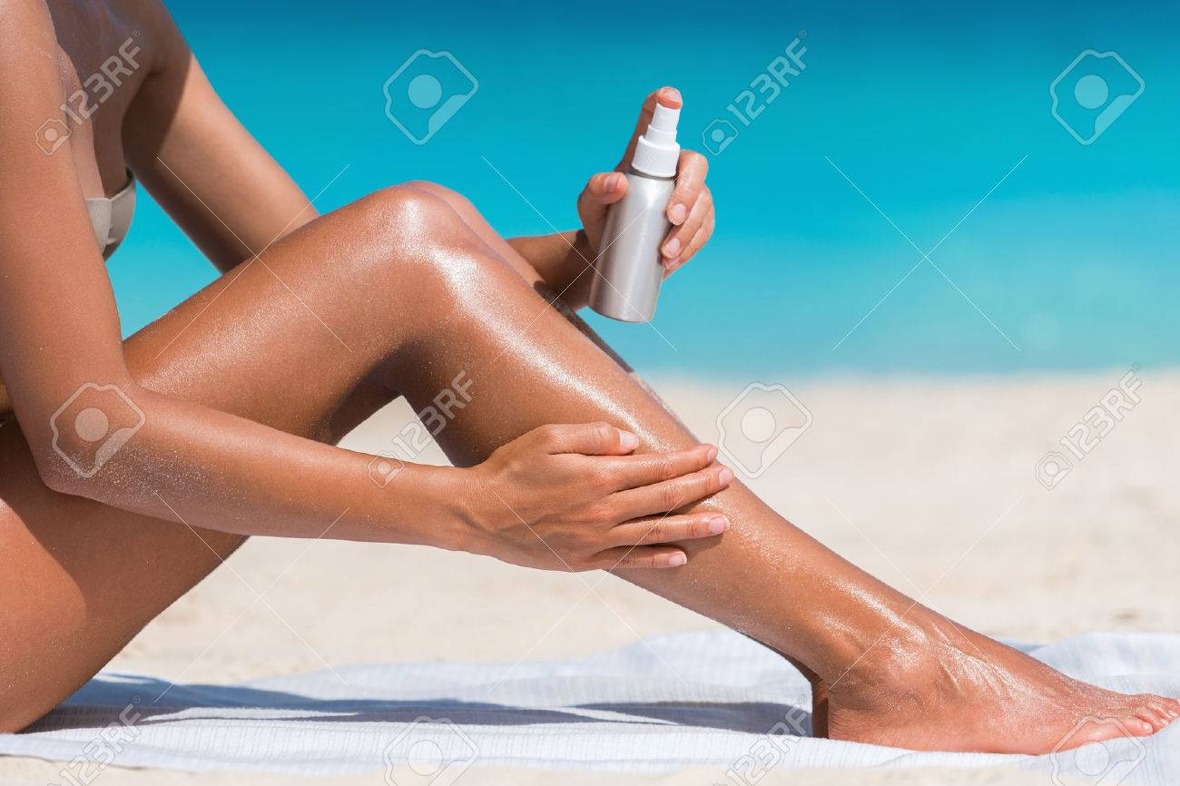 Sunscreen suntan lotion in spray bottle. Young woman in spraying tanning oil on her leg from bottle. Lady is massaging sunscreen lotion while sunbathing at beach. Female model during summer vacation. Stock Photo - 57342435