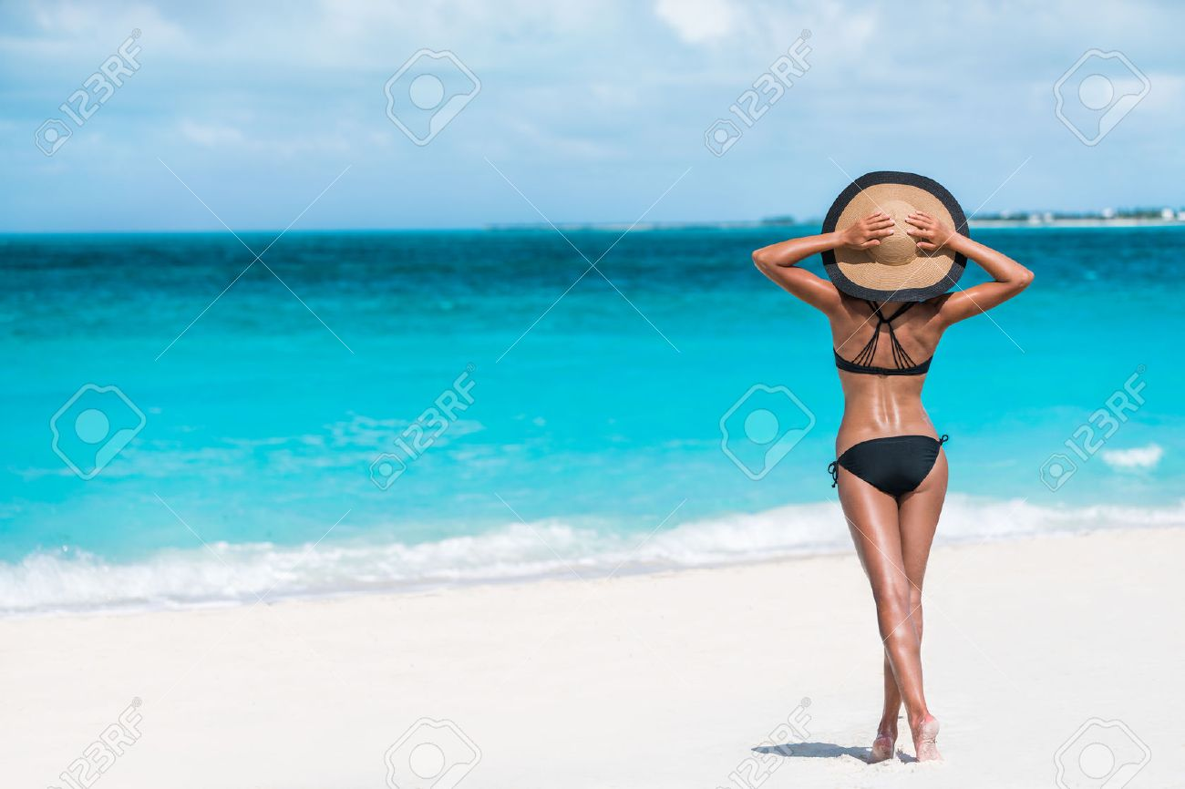 Summer vacation happiness carefree joyful woman standing on white sand enjoying tropical beach destination. Holiday bikini girl relaxing from behind holding straw hat on Caribbean vacation sea water. Stock Photo - 57342442