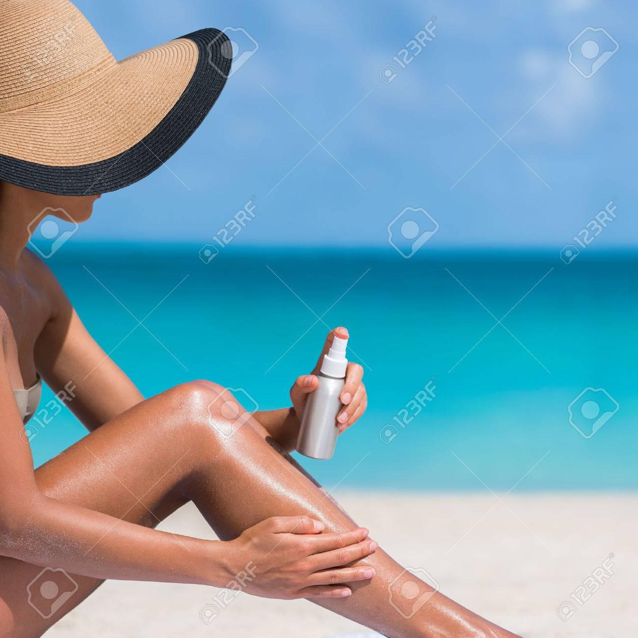 Plage hâle corps vacances Voyage de soins de la peau. Bikini chapeau femme d'appliquer la lotion solaire mettre la crème sur les jambes sexy tannées bronzer bronzage assis sur le sable avec bleu turquoise océan fond. Banque d'images - 56700667