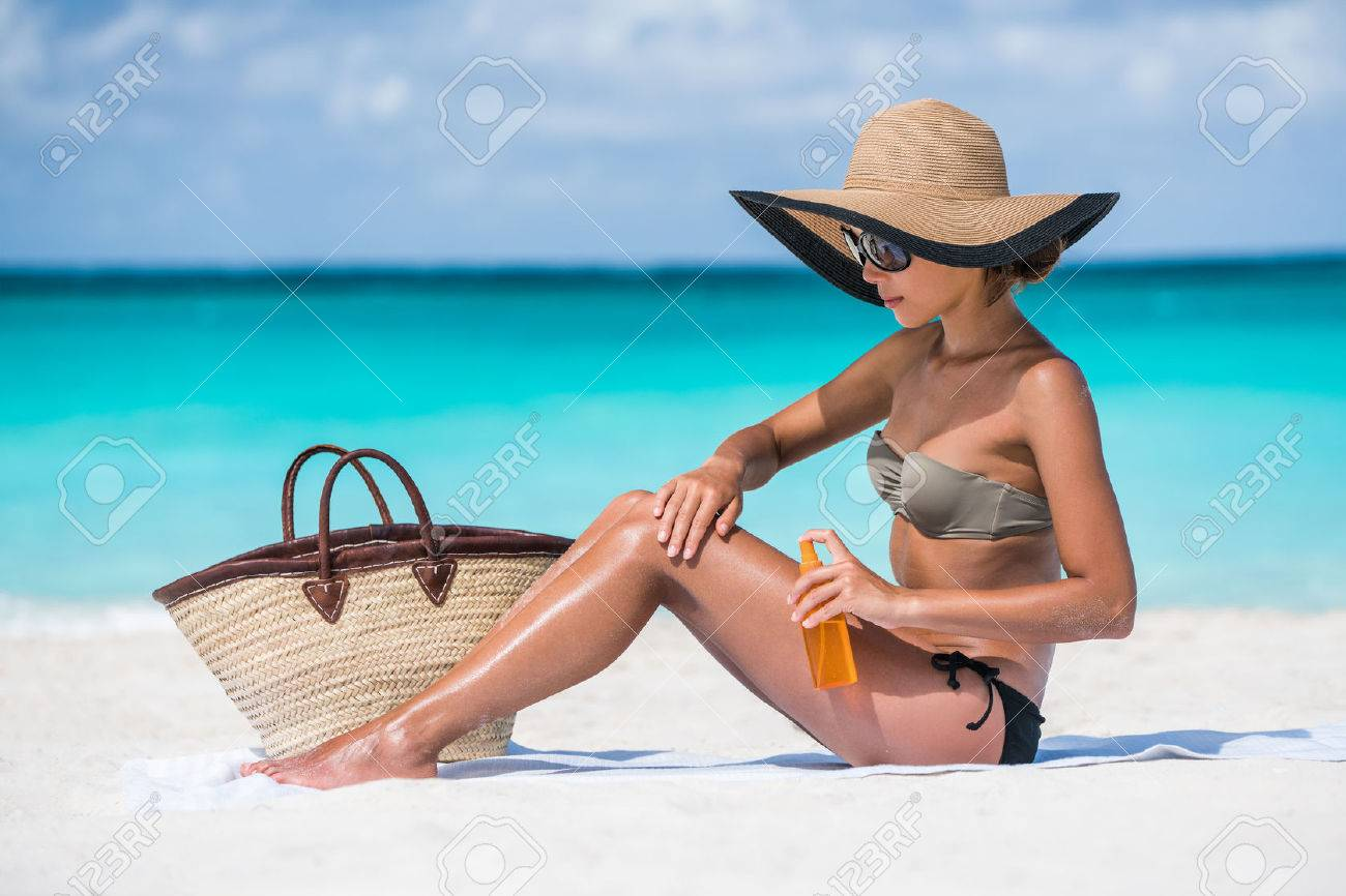 Beach accessories essentials for a summer holiday tropical vacation: sunglasses, straw hat, tote bag, towel, sunscreen. Sexy bikini woman applying sunblock sun protection lotion on Caribbean travel. Stock Photo - 56700668