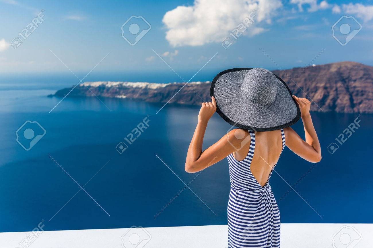 Europe summer vacation travel destination luxury living woman looking at view of Mediterranean Sea and Santorini island Oia village. Elegant tourist lady in fashion back dress and floppy sun hat. Stock Photo - 56700680