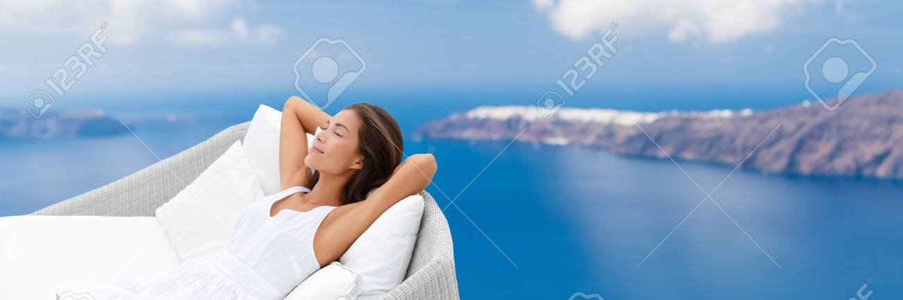 Relaxing woman sleeping on outdoor daybed patio furniture enjoying view of Mediterranean sea Europe travel destination. Asian girl lying down on pillows dreaming carefree happy. Luxury home living. Banque d'images - 56700683