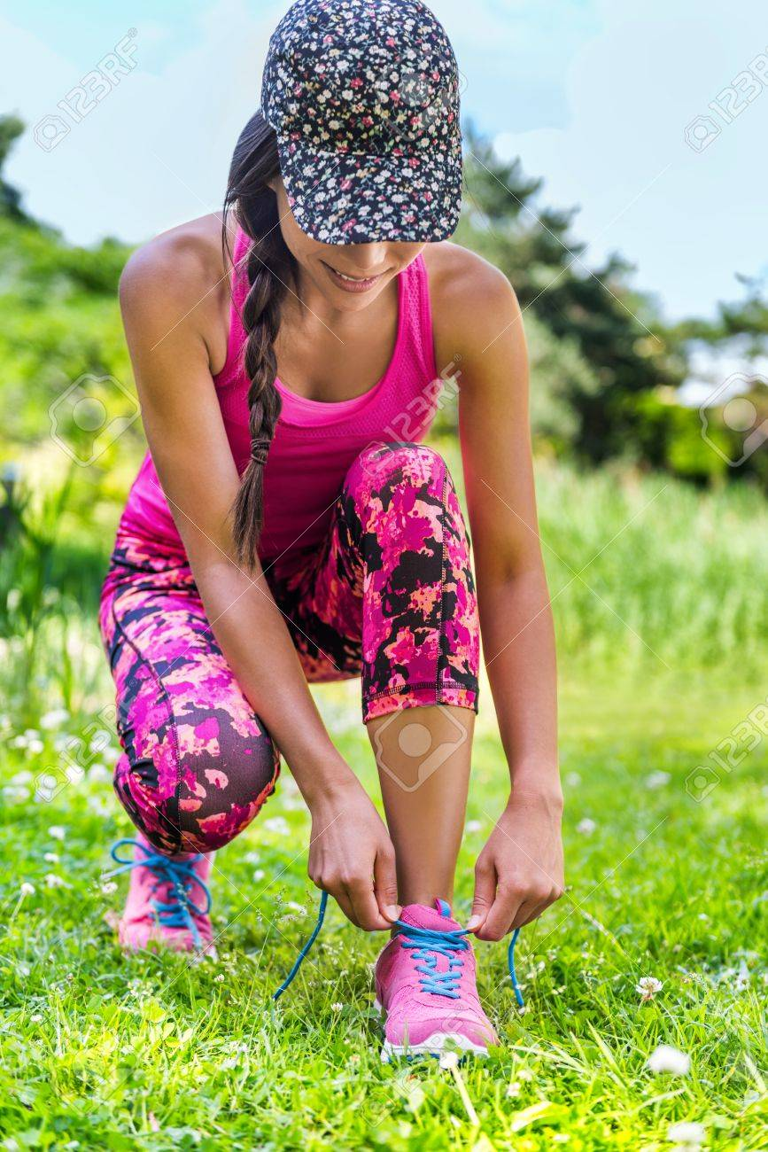 fe55f5ccbd9b7 Cute sporty runner girl in fashion activewear wearing floral cap and pink  leggings outfit getting ready
