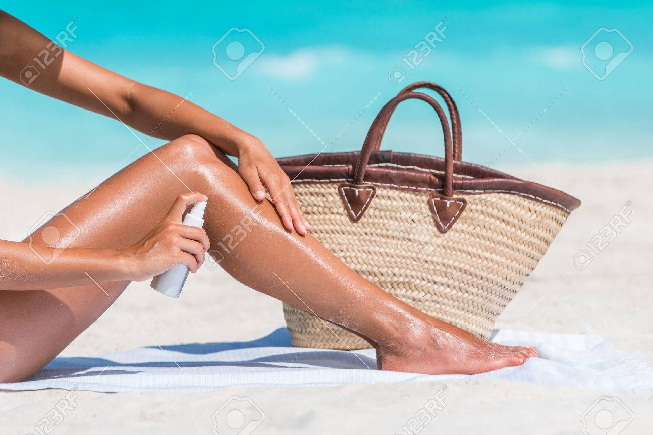 Sunscreen suntan lotion spray skincare product closeup of woman putting tanning oil on legs. Hand holding sunblock or mosquito repellent bottle spraying on body sunbathing at beach summer vacation. Stock Photo - 57342474
