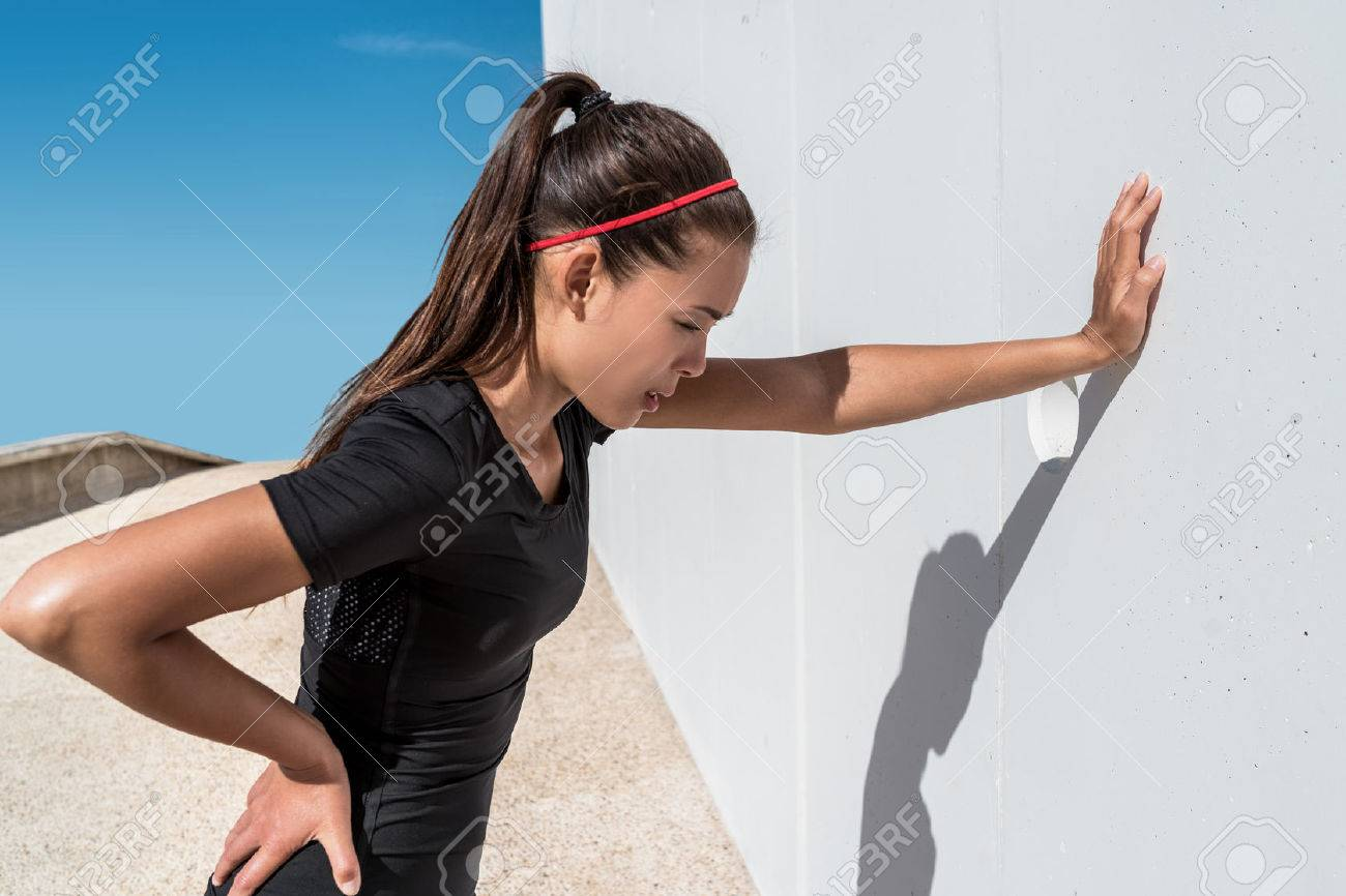 Tired athlete runner exhausted of cardio workout breathing hard after difficult exercise. Asian fitness woman running sweating of heat exhaustion leaning on wall of muscle back pain or cramps. Stock Photo - 57254448