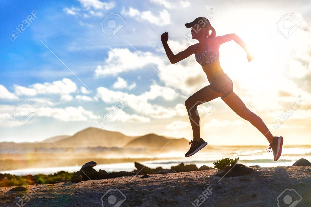 Athlete runner trail running on summer beach. Fit body silhouette of sports Woman in sportswear cap sprinting with energy and motion in outdoors nature training cardio with jogging workout exercise. - 57254459