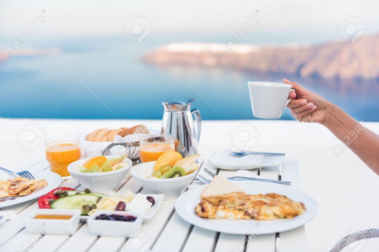 Morning person drinking coffee cup at breakfast table with mediterranean sea view. Woman eating at restaurant outside terrace patio on Santorini, Greece, Europe destination summer vacation. Banque d'images - 57254463
