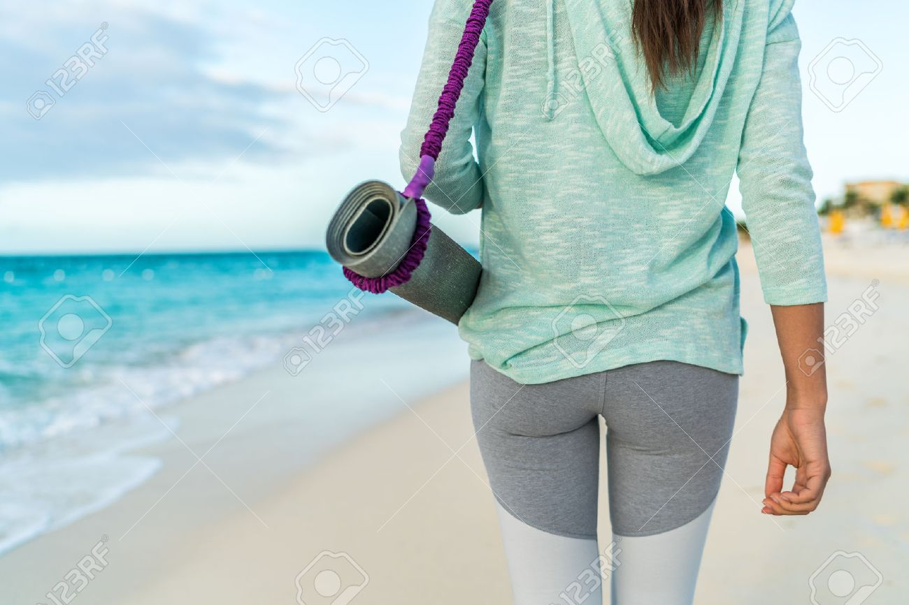 Fitness woman carrying yoga mat with strap on beach going to class training. Closeup of sports equipment, back view of fit athlete in activewear showing fashion leggings and turquoise hoodie. Stock Photo - 57342495