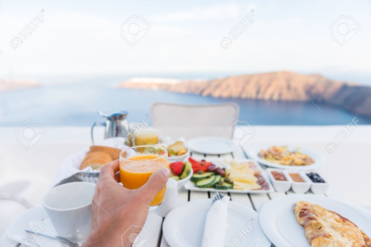 European vacation healthy breakfast food selfie. POV of man drinking morning orange juice at resort restaurant. Table for two on outdoor hotel balcony caldera view on Oia Santorini, Greece, Europe. Stock Photo - 57254479