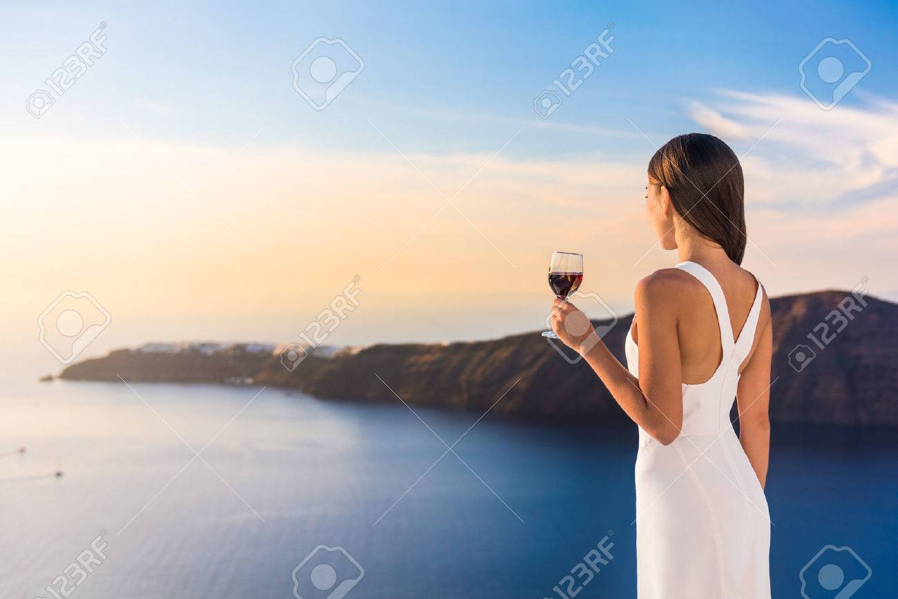 Young woman drinking red wine on outdoor terrace watching beautiful sunset view of Mediterranean Sea. Female in white sundress on summer Europe travel vacation in Santorini, Greece. Stock Photo - 57342499