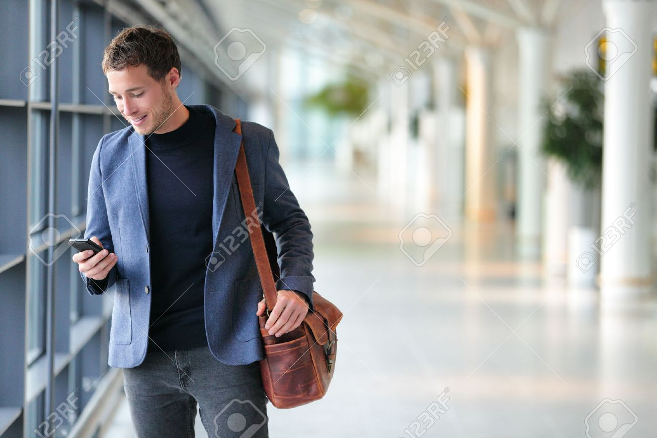 Business man using mobile phone app in airport. Young business professional man texting smartphone walking inside office building or airport terminal. Handsome man wearing stylish suit jacket indoors. - 65498953