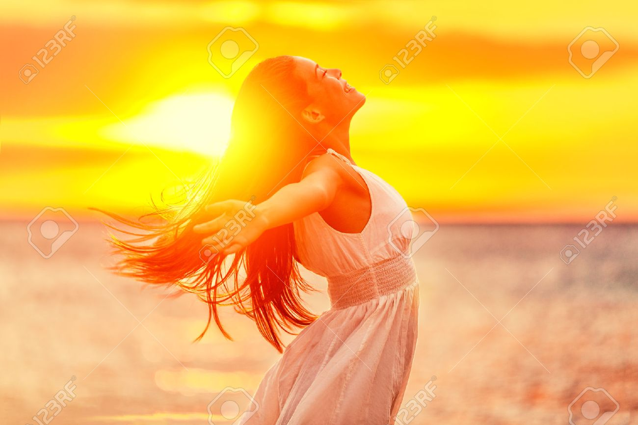 Happy woman feeling free with open arms in sunshine at beach sunset. Freedom and carefree enjoyment girl enjoying life. Beautiful woman in white dress for success, health, hope and faith concept. Banque d'images - 65499160