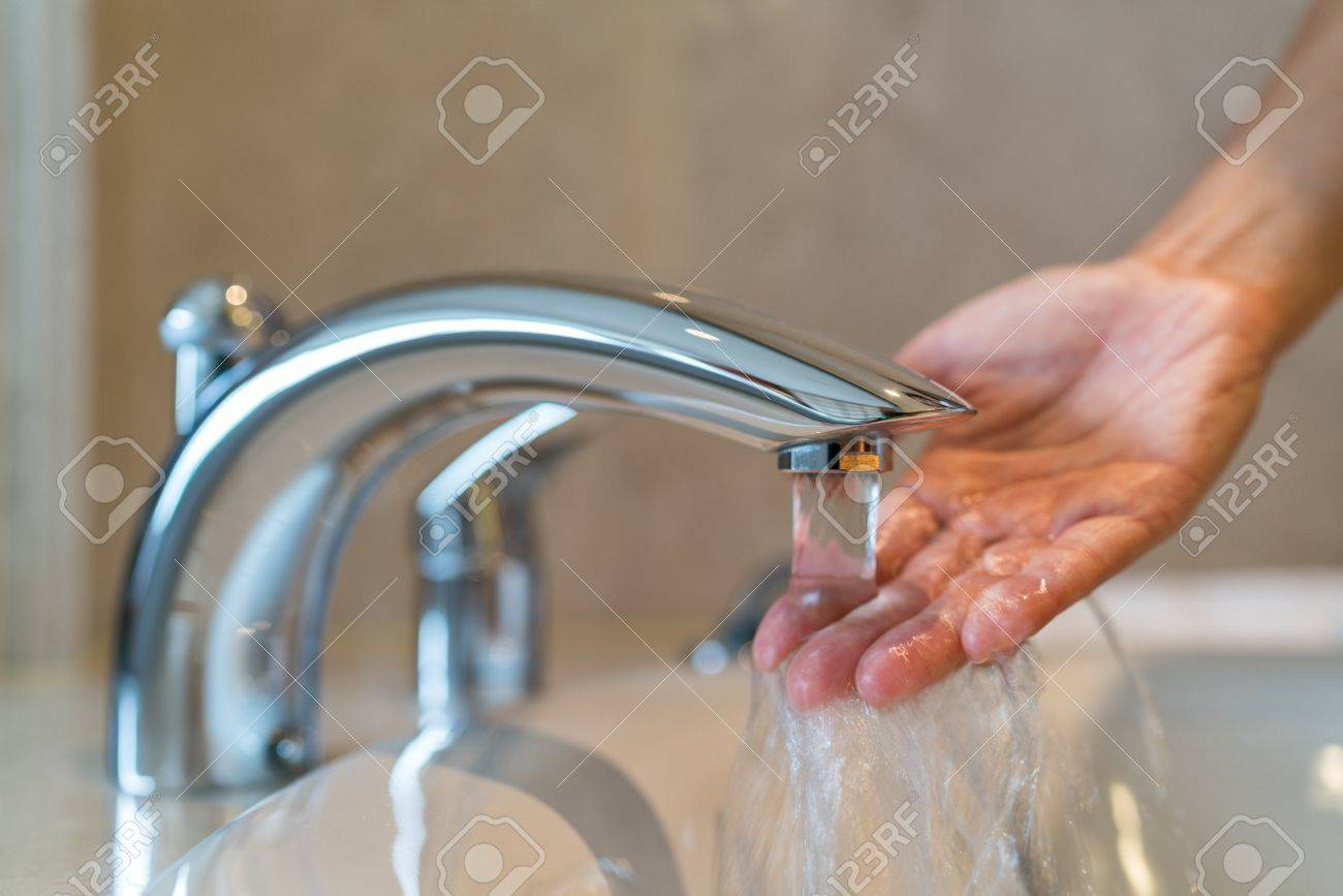 Woman taking a bath at home checking temperature touching running water with hand. Closeup on fingers under hot water out of a faucet of a sink or bathtub in house bathroom Stock Photo - 65604191