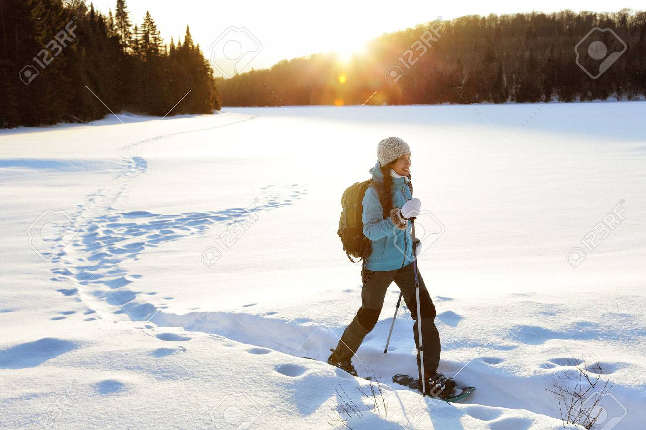 Winter sport activity. Woman hiker hiking with backpack and snowwhoes snowshoeing on snow trail forest in Quebec, Canada at sunset. Beautiful landscape with coniferous trees and white snow. Stock Photo - 65774028