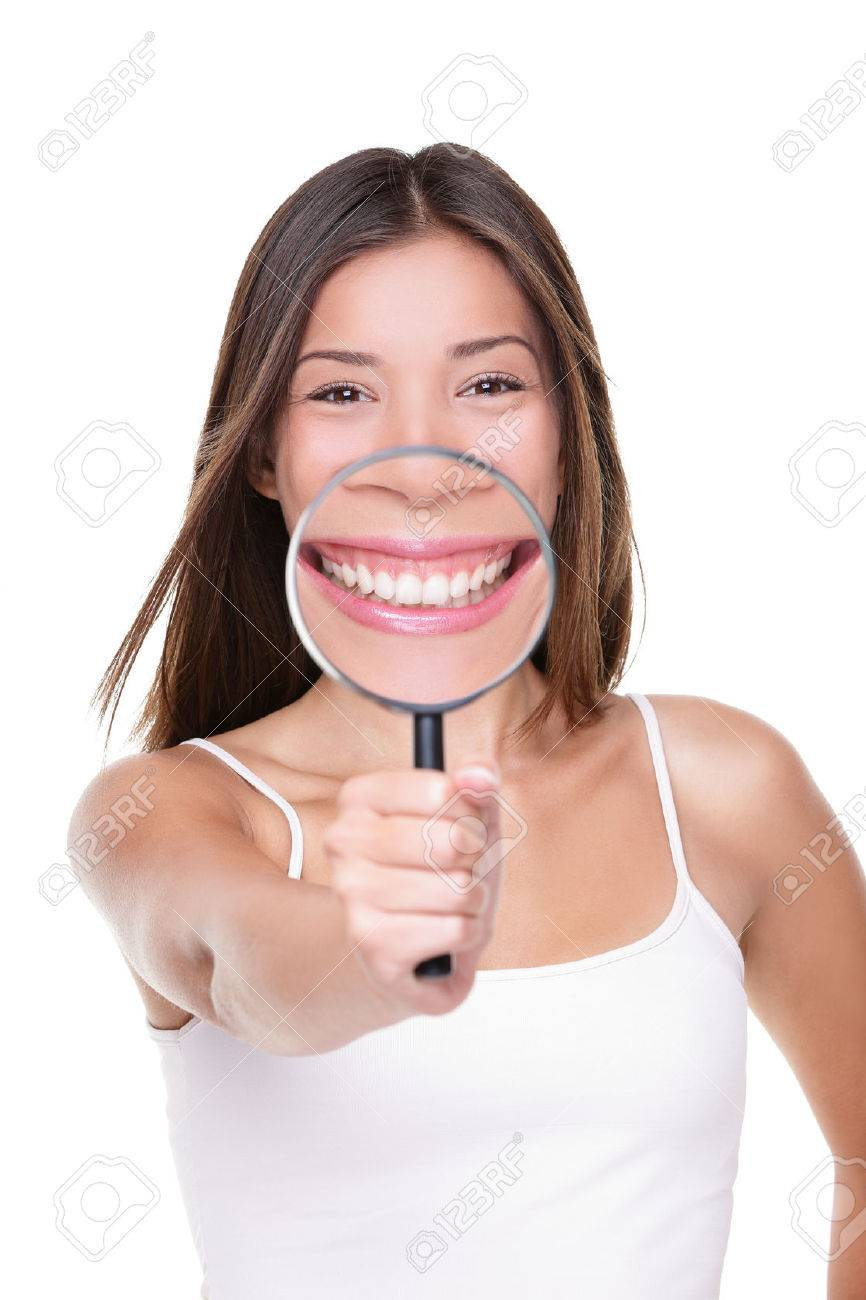 Funny woman showing perfect smile and white teeth with magnifying glass for closeup dental concept. Asian girl inspecting details of mouth showing healthy tooth care for dentist. - 65774036