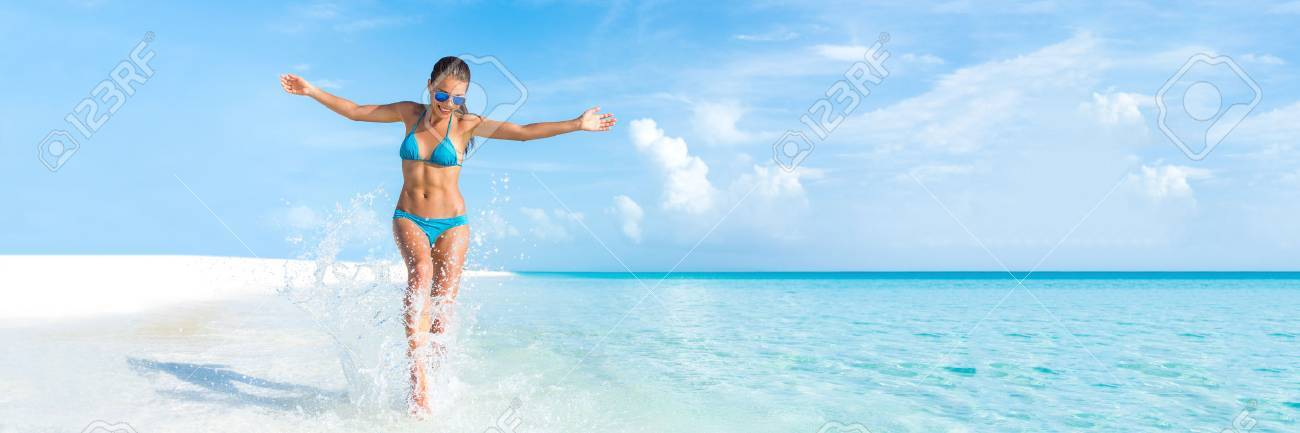Sexy bikini body woman playful on paradise tropical beach having fun playing splashing water in freedom with open arms. Beautiful fit body girl on travel vacation. Banner crop for copyspace. Stock Photo - 67023657
