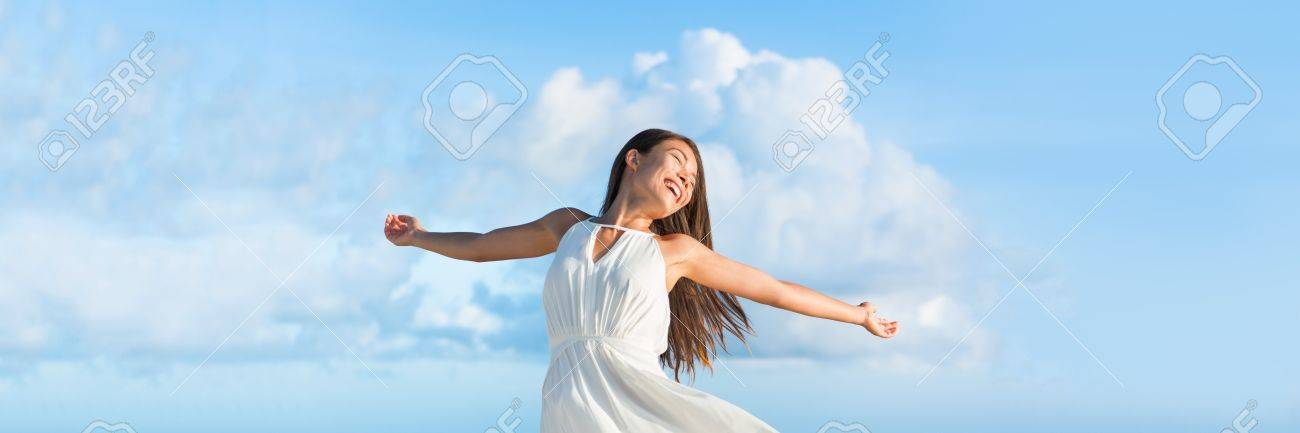 Serene free Asian woman with open arms in freedom or success on sky clouds panorama horizontal banner crop for copyspace. Serenity or bliss. Stock Photo - 66748683