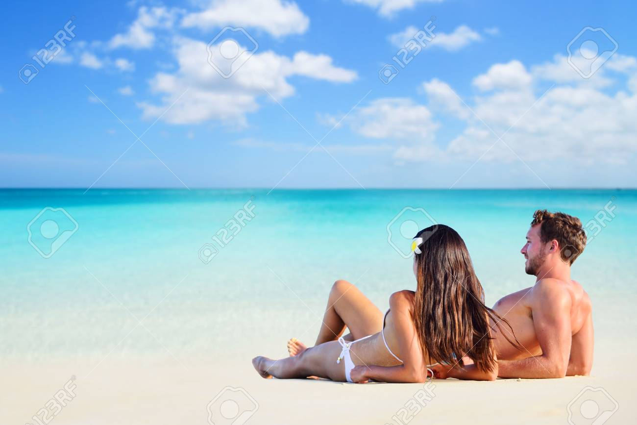 Happy Couple Relaxing Sun Tanning On Vacation Beach Lying Down White Sand Looking At Ocean