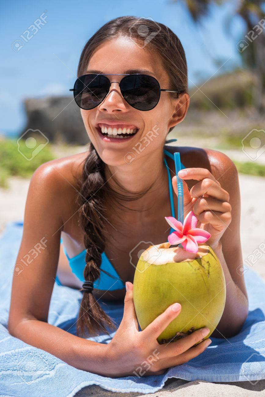 b4f9dcd63ce Happy beach girl with sunglasses having fun drinking fresh coconut water on  summer vacation. Tropical