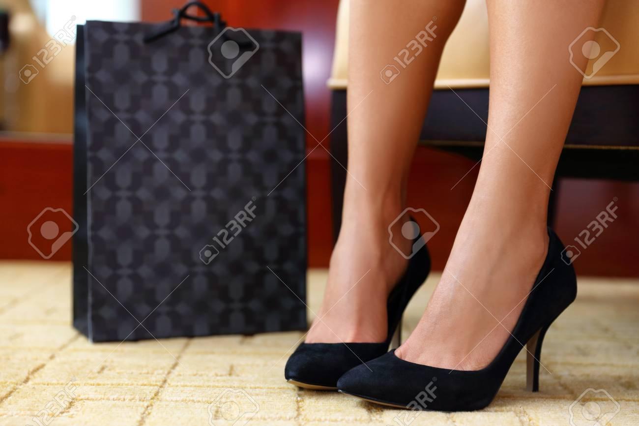 ff5fa63e3de8d Stock Photo - Woman buying new shoes. Closeup female feet wearing black  suede high heels next to shopping bag