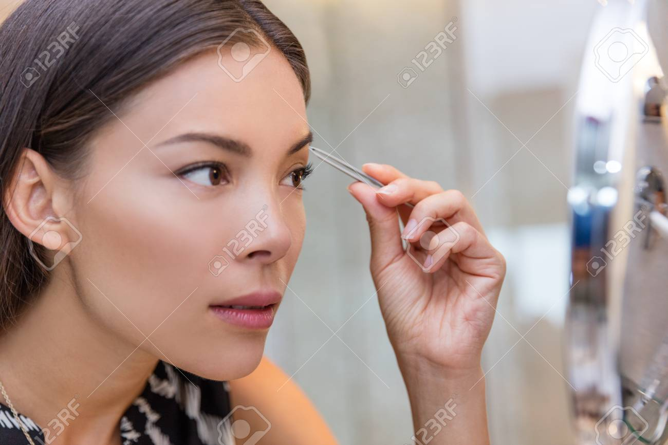 Asian Woman Plucking Eyebrows With Tweezers Using Eyebrow Tweezer