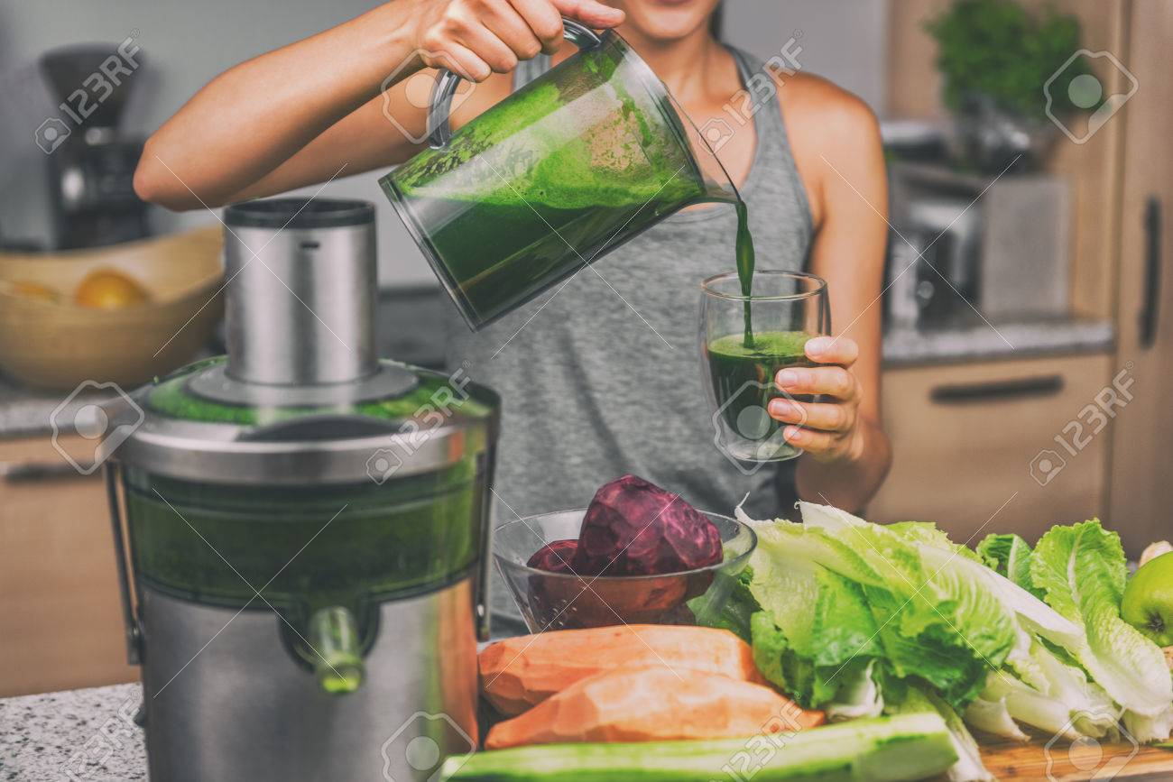 Stock photo woman juicing making green juice with juice machine in home kitchen healthy detox vegan diet with vegetable cold pressed extractor to extract