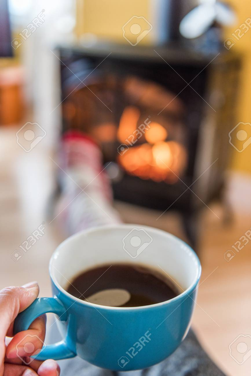 Cozy autumn lifestyle woman drinking coffee relaxing by fireplace