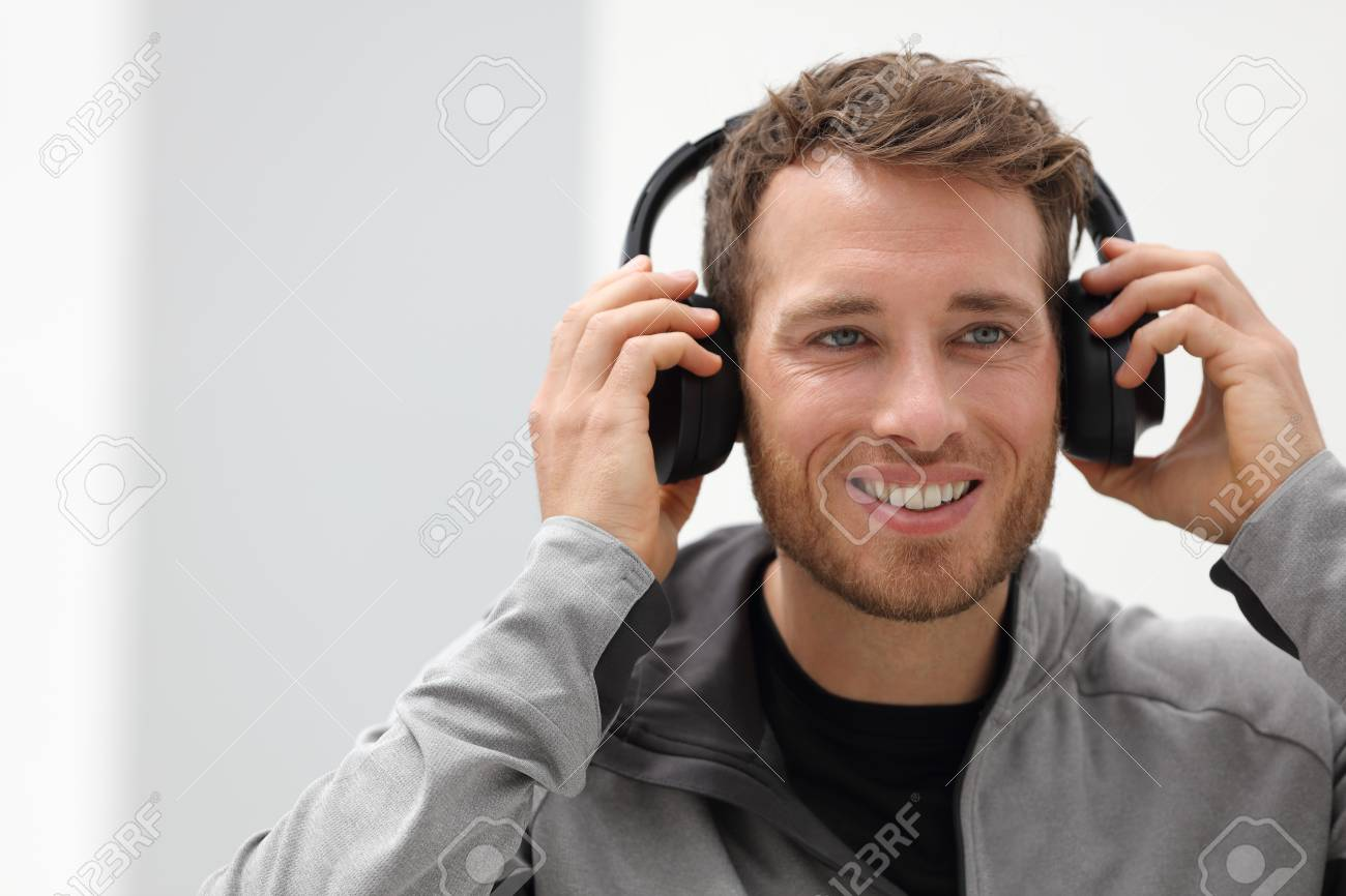 Man putting on headphones to listen to music mobile phone app. Happy smiling young urban person wearing headset sing smartphone mobile app listening to songs in living room at home. - 90920641