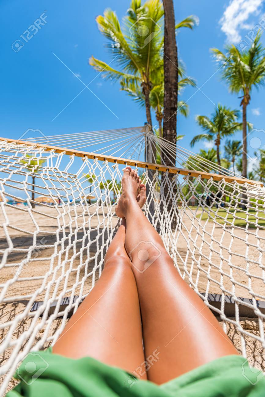 Beach hammock vacation woman feet selfie. Girl relaxing taking pov picture  of her legs and