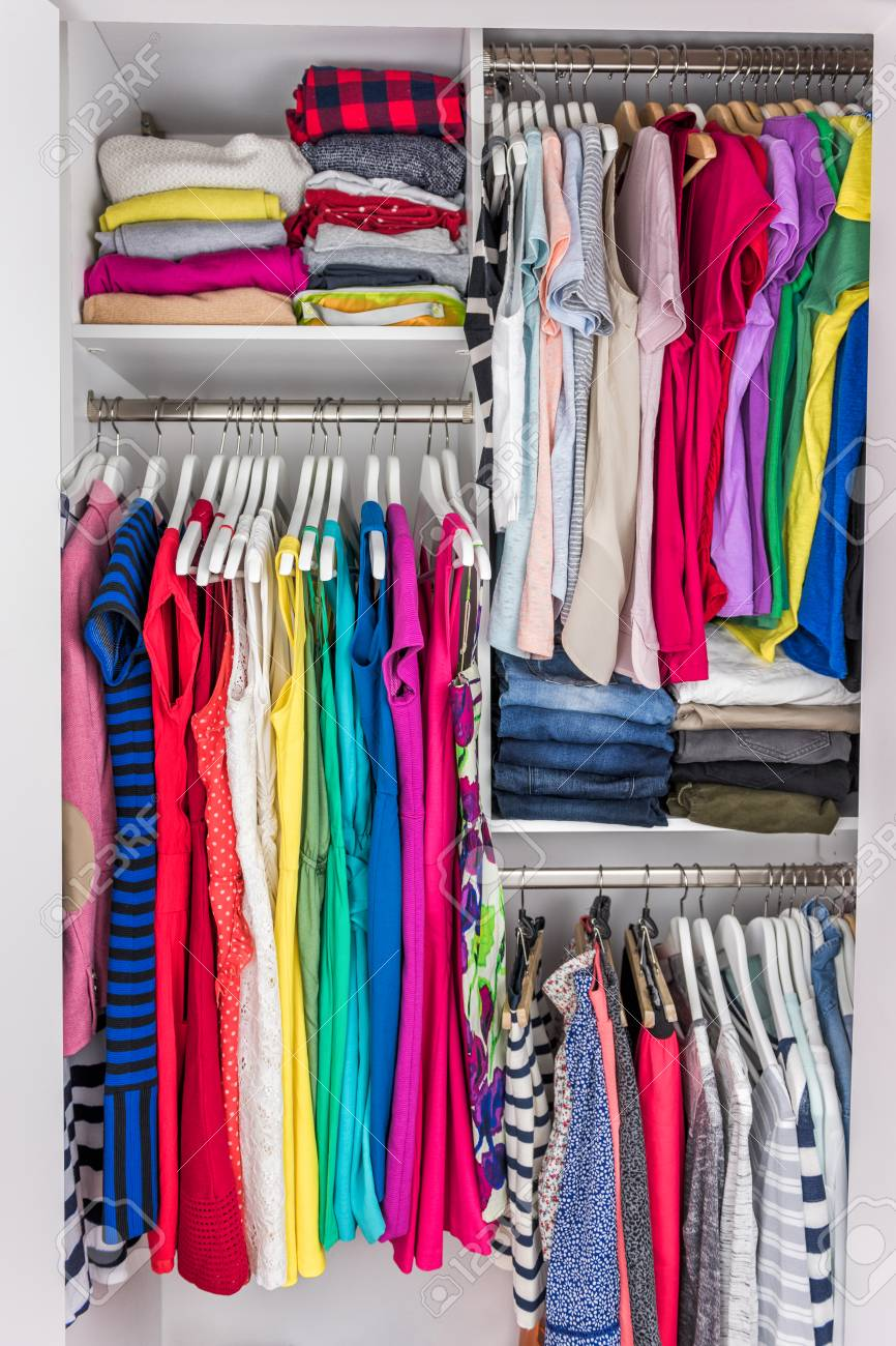 061ee2d14b Home closet organized walk-in bedroom wardrobe of women fashion clothes  hanging on racks.