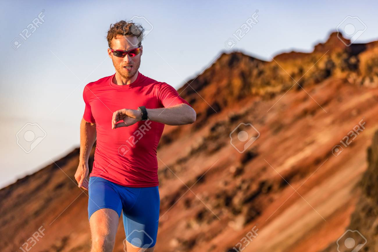 Athlete runner checking cardio on sports smartwatch jogging on
