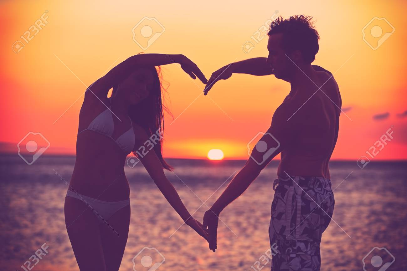 Love At Sunset Couple Making Heart Shape With Arms Holding Hands