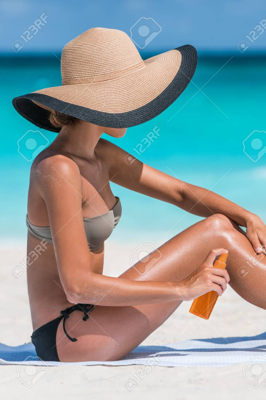 Sexy bikini woman putting suntan lotion oil on tanned skin. Girl tourist  applying sunblock cream