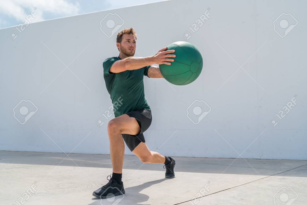 Working out man training legs and core ab workout doing lunge twist exercise with medicine ball weight. Gym athlete doing lunges and torso rotations for abs training. - 96290976